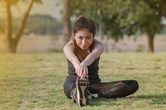 Scaldarsi atletico dell'asiatico della donna e giovane seduta dell'atleta femminile Immagine Stock Libera da Diritti