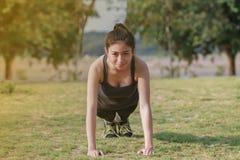 Scaldarsi atletico dell'asiatico della donna e giovane seduta dell'atleta femminile Fotografia Stock Libera da Diritti