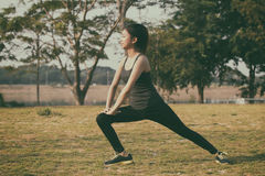 Scaldarsi atletico dell'asiatico della donna e giovane seduta dell'atleta femminile Fotografia Stock