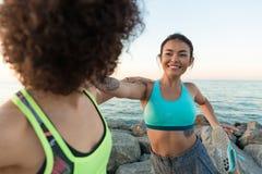 Scaldarsi sorridente di due giovane donne di forma fisica Fotografia Stock Libera da Diritti