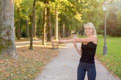 Scaldarsi sportivo sorridente della giovane donna Fotografie Stock