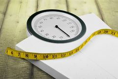 Bathroom scale with a measuring tape, close-up. Scale bathroom measuring tape bathroom scale background object number Royalty Free Stock Photography