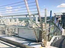 Scale brillanti del grande cromo del metallo con le inferriate sul tetto di un grattacielo di vetro, un edificio alto con una vis fotografia stock libera da diritti