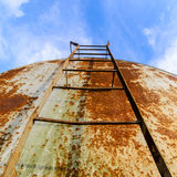 Scale corrose ed arrugginite del barilotto di stoccaggio di petrolio contro la bella b Fotografia Stock