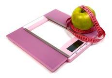 Scale del pavimento che misurano nastro e mela verde Immagine Stock