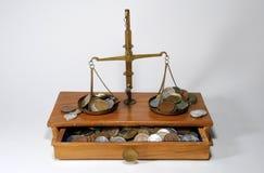 Scale dell'equilibrio con le monete Fotografia Stock Libera da Diritti