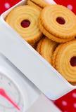 Scale della cucina con il concetto di dieta dei biscotti dell'ostruzione Fotografie Stock