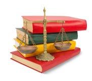 Scale di giustizia in cima ai libri legali sopra bianco Immagini Stock