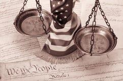 Scale di giustizia, della bandiera americana e della costituzione degli Stati Uniti Fotografia Stock
