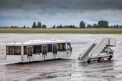 Scale di imbarco del bus e del passeggero di navetta al grembiule dell'aeroporto Fotografia Stock