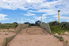 Scale di legno accanto alle piante dell'aloe ed alla vegetazione della duna Immagine Stock