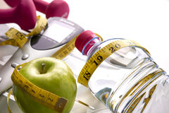 Scale with dumbbells bottle apple and tape measure elevated view Stock Image