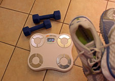 Scale, dumbbells and shoes Stock Images