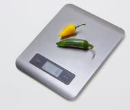 Scale elettroniche della cucina con i peperoni Fotografia Stock