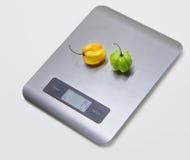 Scale elettroniche della cucina con i peperoni Immagine Stock