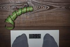 Scale elettroniche sull'essere a dieta di legno del pavimento Immagini Stock Libere da Diritti