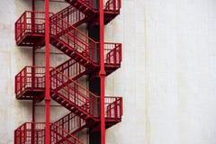 Scale esterne rosse di emergenza su una parete bianca Fotografia Stock