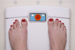 Scale with Feet Emoji Mad. Digital Bathroom Scale Displaying an Angry Emoji stock image