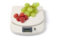 Scale and Fruits. Scale with raspberries and grapes isolated over a white background. Check other photos in the serie stock photo