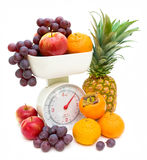 Scale and fruits  on white background Royalty Free Stock Images