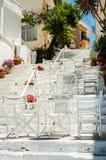 Scale greche bianche con le tavole e le sedie Via greca tipica Fotografia Stock Libera da Diritti
