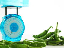 Scale for health. Kitchen scale and green peppers on white back Royalty Free Stock Images