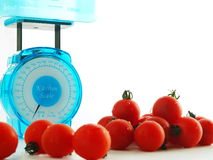 Scale for health. Kitchen scale and tomatoes on white back Royalty Free Stock Images