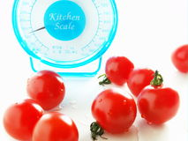 Scale for health. Kitchen scale and tomatoes on white back Royalty Free Stock Image