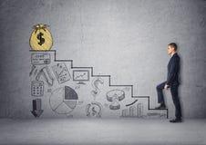 Scale rampicanti dell'uomo d'affari con i grafici economici Fotografie Stock Libere da Diritti