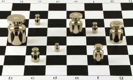 Scale steel shiny weights on chessboard surface Stock Photography