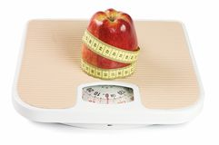 Scale, tape and apple Royalty Free Stock Photos