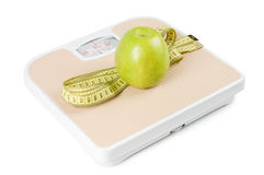 Scale, tape and apple on white Royalty Free Stock Photography
