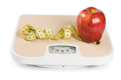 Scale, tape and apple on white Stock Photos