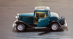 Scale toy model Ford Coupe. A petrol blue scale toy model of a 1932 Ford 3-window Coupe with door open - side view Stock Image