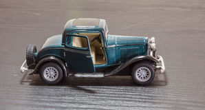 Scale toy model Ford Coupe. A petrol blue scale toy model of a 1932 Ford 3-window Coupe with door open - side view Royalty Free Stock Photo