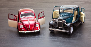 Scale toy model Ford Coupe and VW Beetle. Scale toy models of Petrol blue 1932 Ford 3-window Coupe and 1967 red and white VW Volkswagen Beetle with doors open Stock Images