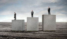 Scale of values. Three businessmen standing on cubes of different height Stock Images