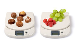 Scale on White. Scale with fruits and junk food isolated over a white background royalty free stock image