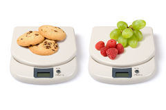 Scale on White. Scale with fruits and junk food isolated over a white background royalty free stock photography