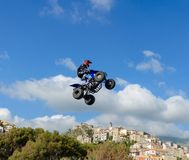 The freestyle Quad bike pilot makes a jump with a high jump with a trick. Royalty Free Stock Photo