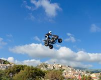 The freestyle Quad bike pilot makes a jump with a high jump with a trick. Royalty Free Stock Images