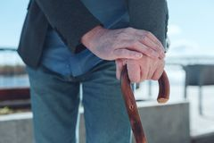 Scaled up look on old male hands crossing over walking cane royalty free stock photos