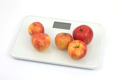 Scales with apples 1. Five apples on a scale with a white background Royalty Free Stock Photo