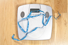 Scales with blue tape measure across it Royalty Free Stock Photo