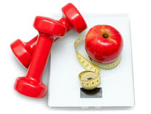Scales, dumbbells, red apple and measuring tape Royalty Free Stock Photos