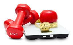 Scales, dumbbells, red apple and measuring tape Stock Photo