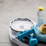 Scales after exercise, slimming aerobics and weight control, copy space. Scales after athletic exercise, slimming aerobics and weight control with dumbbells stock photo