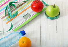 Scales, fruits, water on the  wooden background Stock Image