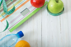 Scales, fruits, water on the  wooden background Stock Images
