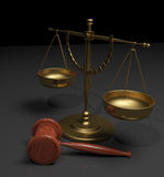 Scales and gavel. Gold or brass scales of justice and wood gavel on a grey and black background Royalty Free Stock Images